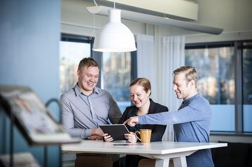 Buildercomin asiantuntijat kahvihuoneessa katsomassa tablettia